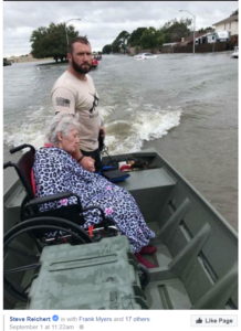 A man driving his hunting, fishing, or otherwise flat-bottom boat with an elderly woman in a wheelchair as his passenger.